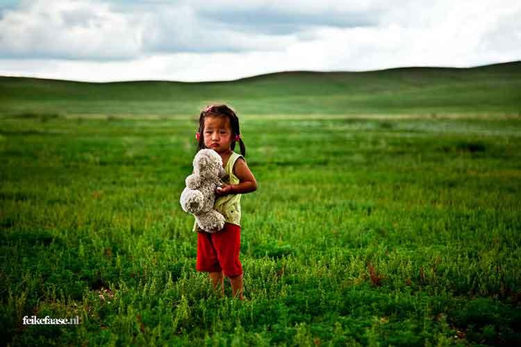 Reisfotografie, kind met knuffel in groen landschap Mongolië- foto door fotograaf Feike Faase