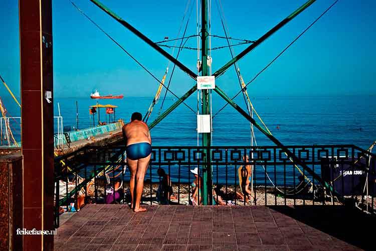 Reisfotografie, man kijkt over blauwe zee naar schip - foto door fotograaf Feike Faase